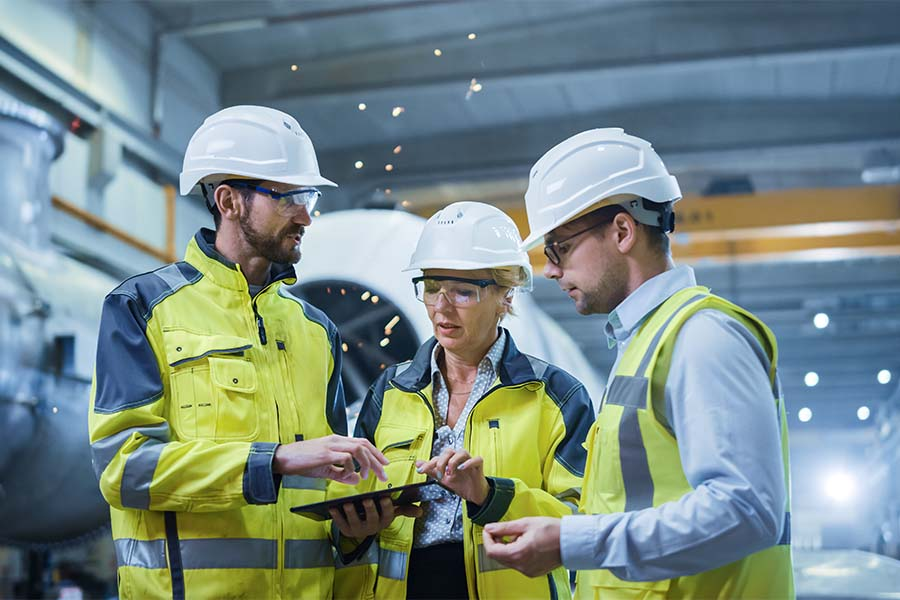 Insurance Quote - Group of Engineers Standing in a Manufacturing Facility Having a Discussion While Using a Tablet
