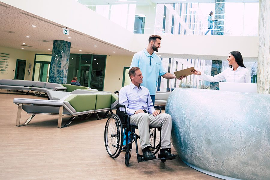 Specialized Business Insurance - View of Senior Man in a Wheelchair in the Hospital Being Attended by a Member of the Medical Staff in the Reception Area