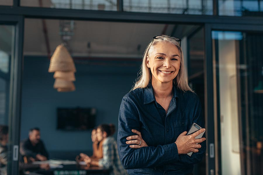Business Insurance - Boss Leaning against a Doorframe in a Large Dark Blue Office, Employees Working at a Conference Table behind Her