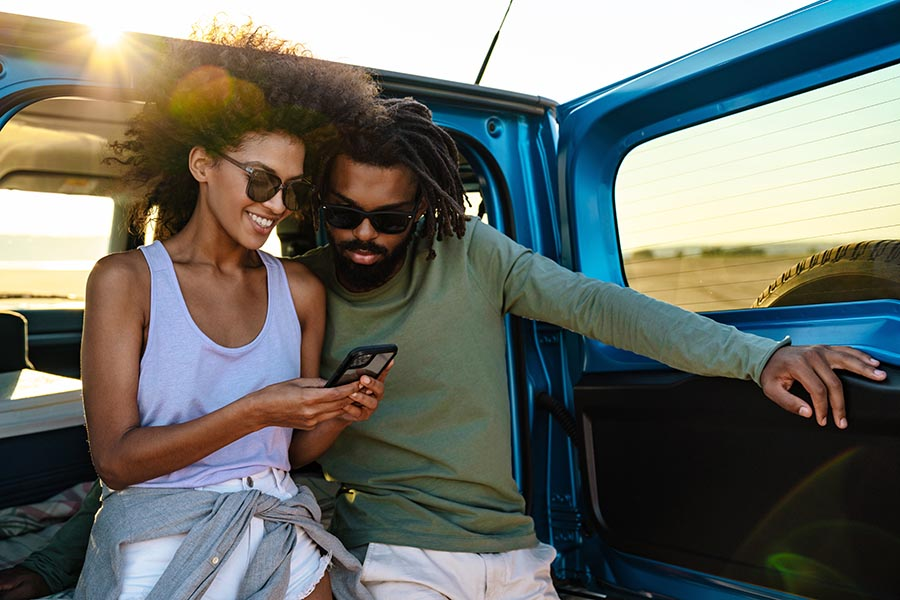 Client Center - Couple Use a Cell Phone While Leaning against the Back of Their Car, Sun Setting behind Them, Dressed for Warm Weather