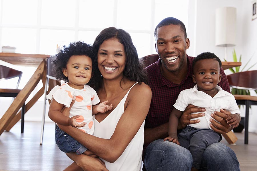 Personal Insurance - Happy Family Sits in Their Home, Kitchen Table Behind Them, Parents Holding Their Baby Daughter and Toddler Son