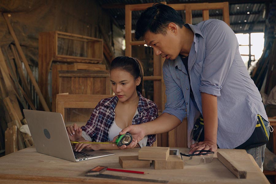 Specialized Business Insurance - Contractors Collaborating over a Laptop and Plans in a Workshop