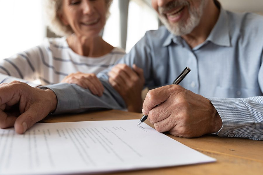 ACA and Short-Term Medical Plans - Close up of a Husband and Wife at a Desk and Smiling