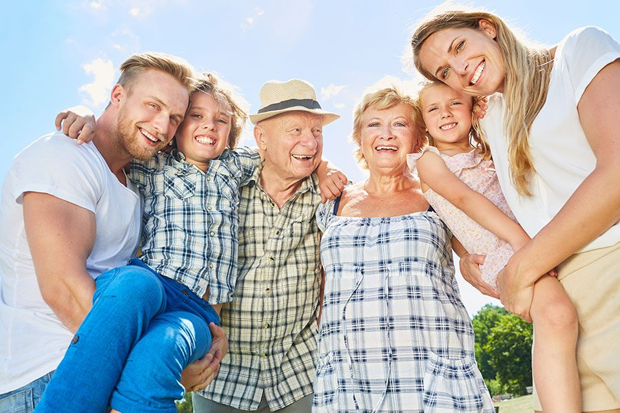 About Our Agency - View of Grandparents, Parents and Children Laughing and Smiling While Embracing Each Other on a Sunny Day