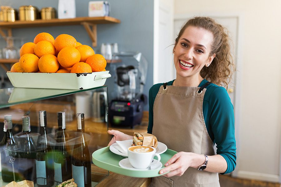 Business Insurance - Woman Wearing a Smok Getting Ready to Serve a Plate of Coffee and Sandwich at a Cafe