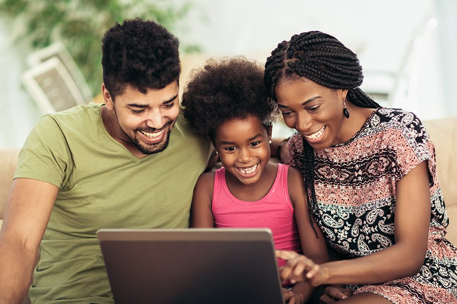 Client Center - Happy Family Sitting Together on a Sofa Using a Laptop to Video Chat