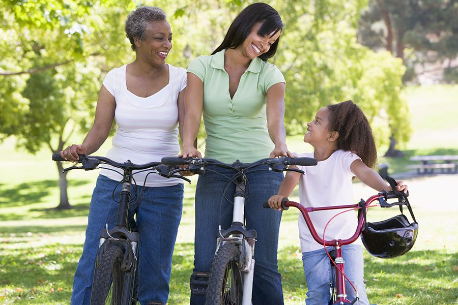 Employee Benefits - Loving Grandmother, Mother and Daughter Taking a Break From Riding Their Bikes at a Park