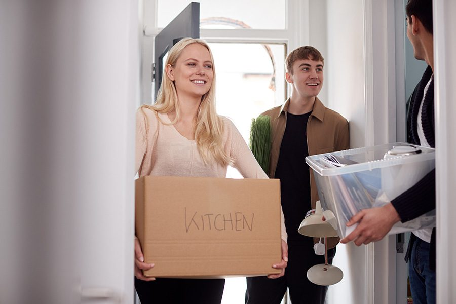 Off-Campus Student Housing Insurance - A Group of College Students Carrying Boxes and Moving into an Off-Campus Accommodation Together
