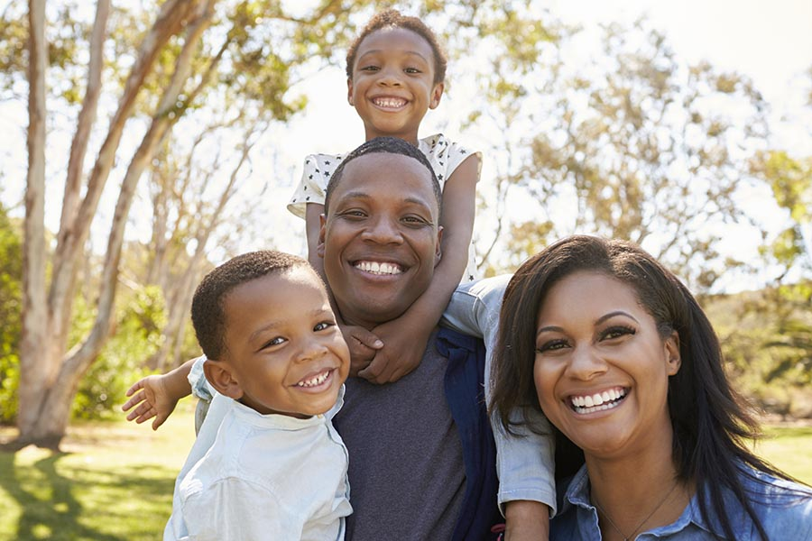 Personal Insurance - Happy Young Family in a Park, Daughter on Dad's Shoulders, All Smiling