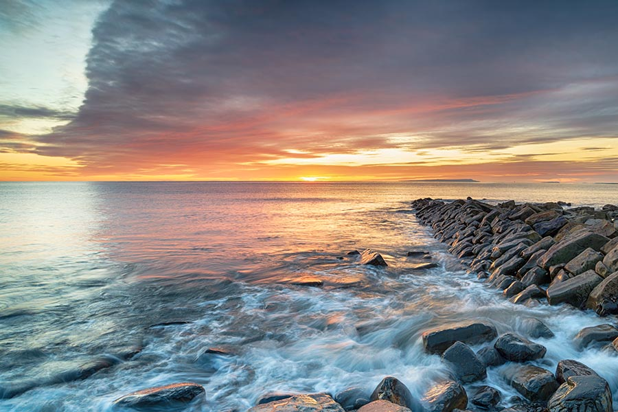 Rocky River, OH Insurance - Rocky Jetty Leading Out Into Blue Water At Sunset, The Sky Turning Bright Orange and Pink