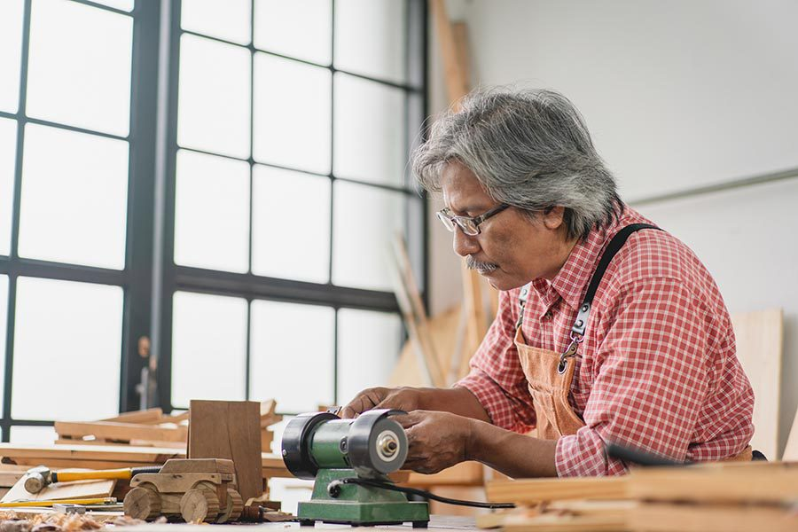 Specialized Business Insurance - Senior Craftsman Uses Tools in a Cluttered Woodshop, Wearing Safety Goggles