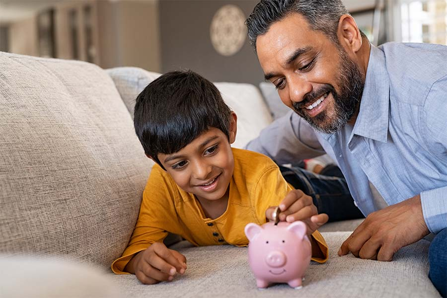 Money Savings Checklist - Closeup Portrait of a Smiling Father Watching His Son Put Coins in a Piggybank at Home