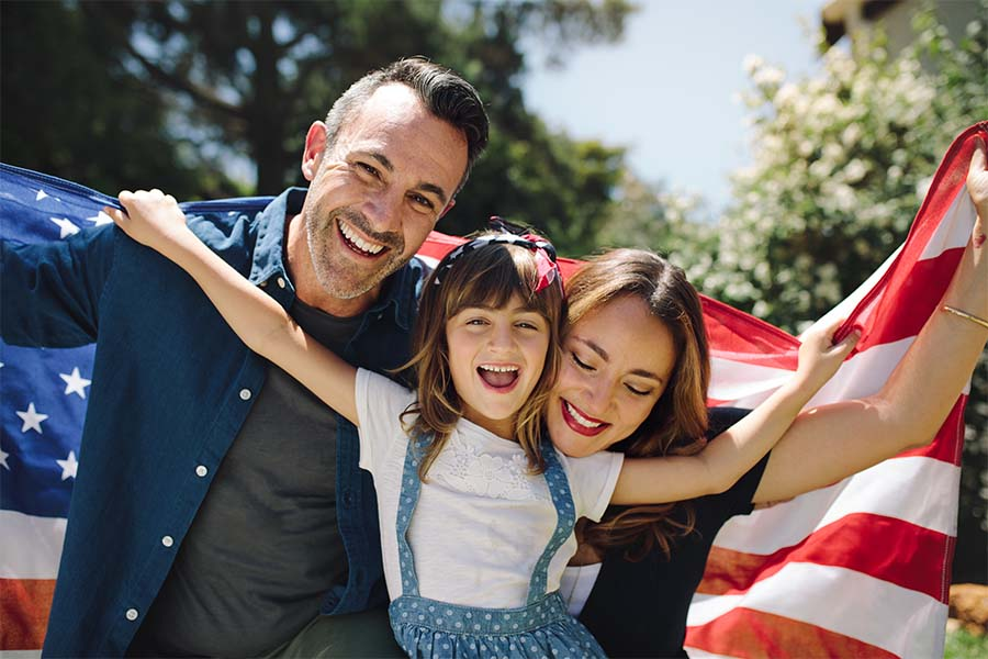 Personal Insurance - Closeup Portrait of a Cheerful Family with a Young Daughter Standing Outside in the Backyard While Holding an American Flag
