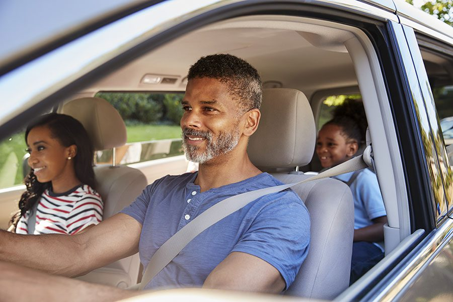 Auto Insurance - View of a Cheerful Family Driving in a Car During a Road Trip