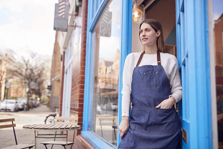 Commercial Insurance - Portrait of a Young Female Small Business Owner Standing Outside Her Cafe on the Main Street