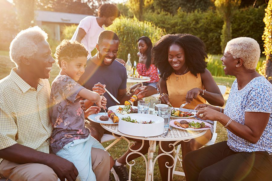 About Our Agency - Multi-Generation Family Eating Outdoors at a Table in the Garden at Sunset