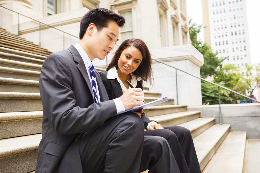 Business Insurance - Two Business Colleagues Sitting On Municiple Steps and Working Together Outdoors