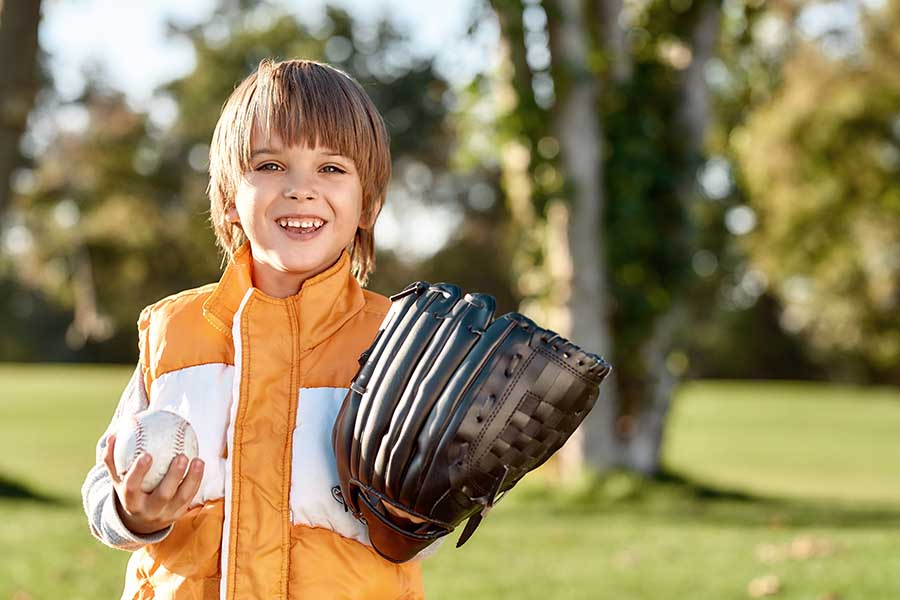 Employee Benefits - Smiling Little Boy Getting Ready to Play Baseball in the Park on a Sunny Day
