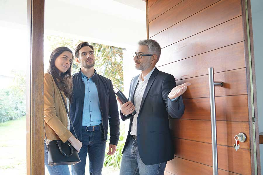 Personal Insurance - Couple with Real-Estate Agent Walking through Front Door of Their New Modern High-End Home