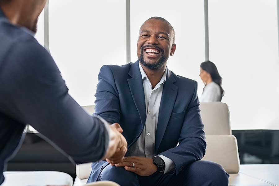 Risk Management - Business Partners Shaking Hands after Concluding a Business Meeting In a Modern Office