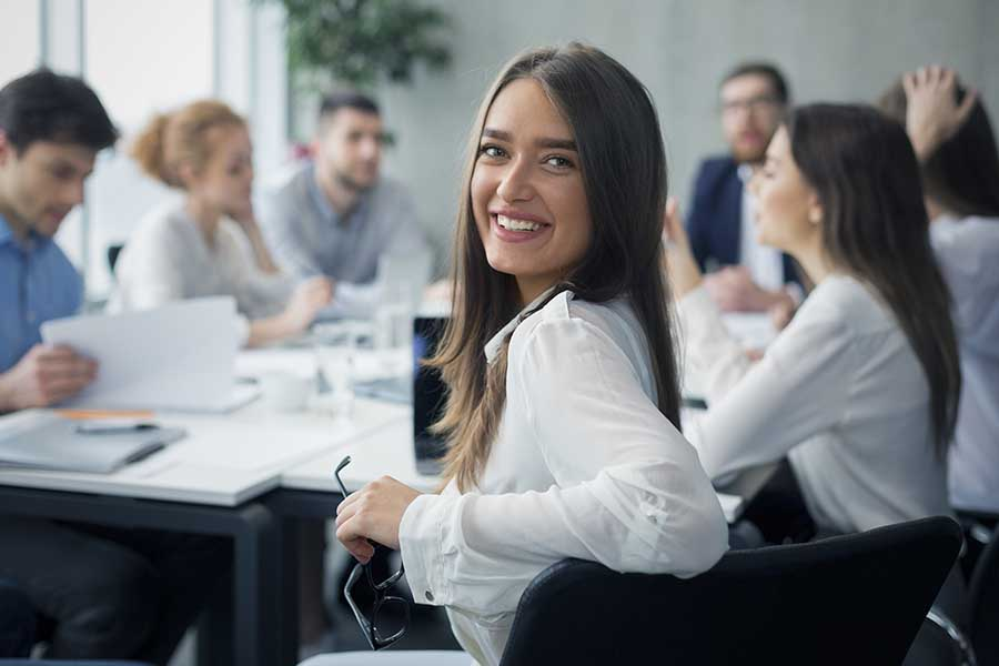 Trusted Partners - Positive Business Woman Smiling at Camera during a Business Meeting In a Large Conference Room