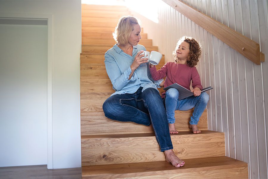 About Our Agency - Portrait of Mother and Daughter Sitting on a Wooden Staircase at Home While They Enjoy a Cup of Tea