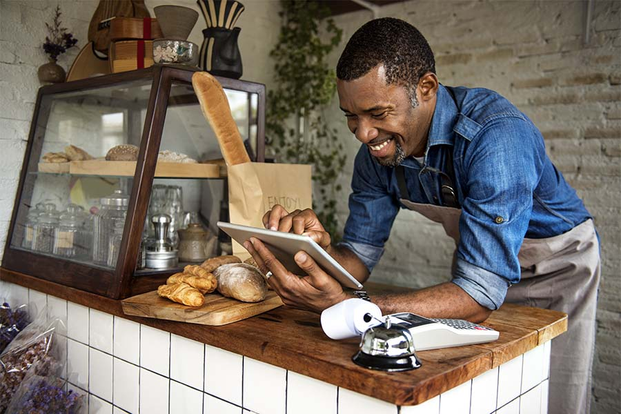 Business Insurance - Closeup Portrait of a Cheerful Middle Aged Bakery Shop Owner Using his Tablet While Standing Behind the Front Counter