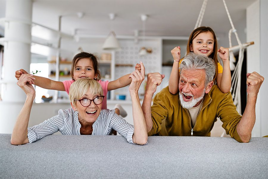 Client Center - Portrait of Cheerful Grandparents Having Fun Playing with Their Granddaughters at Home