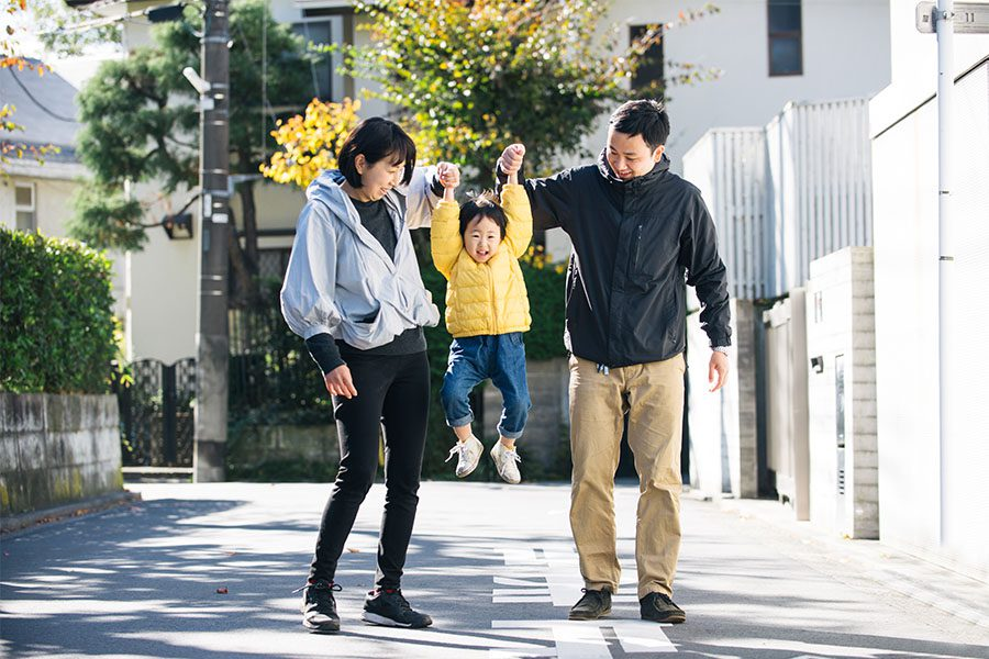 Personal Insurance - Portrait of Two Cheerful Parents Holding Up Their Son in the Air as They Go for a Walk in the Neighborhood on a Sunny Day