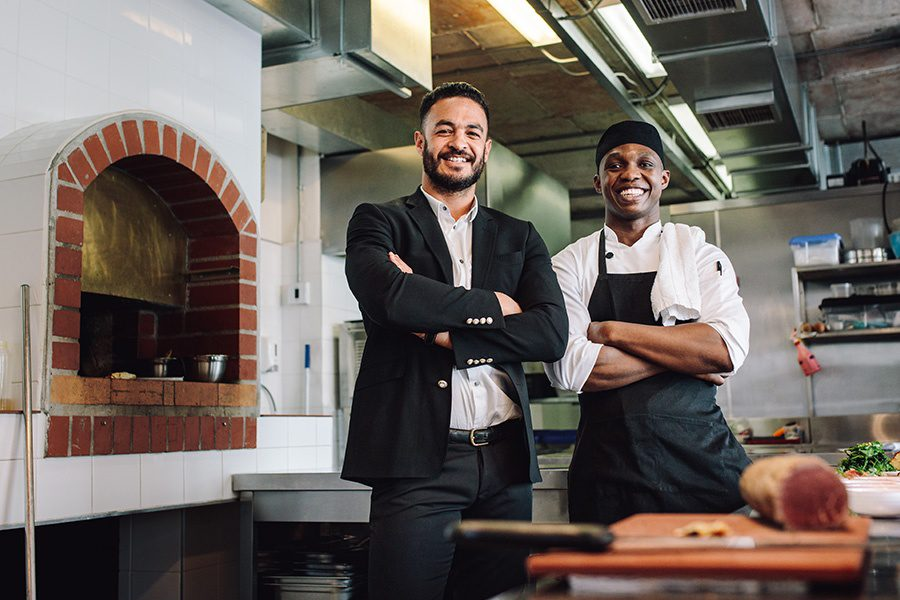 Business Insurance - Restaurant Manager with Chef in Kitchen Smiling by Brick Oven