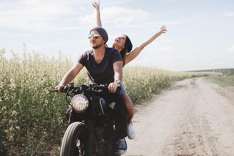 Personal Insurance - a Couple Taking a Ride on a Dirt Road Next to a Wheat Field on a Motorcycle