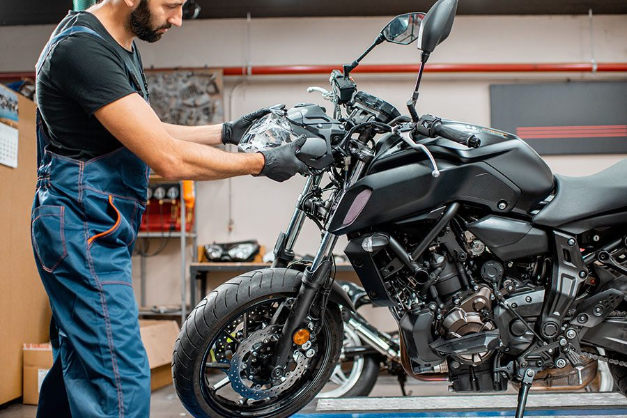 Specialized Business Insurance - Worker Repairing Motorcycle Headlight in the Workshop