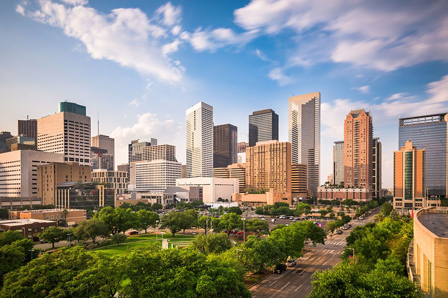 Webster, TX - Skyline View of Houston Texas Displaying Man Buildings and a Park With Trees