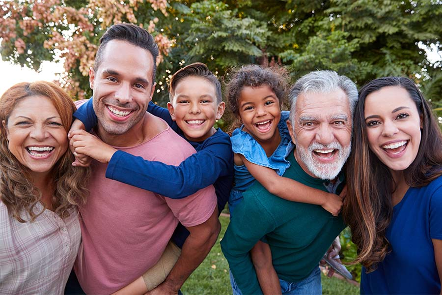 About Our Agency - Closeup Portrait of a Cheerful Extended Multi Ethnic Family with Two Kids Standing Outside on the Green Grass