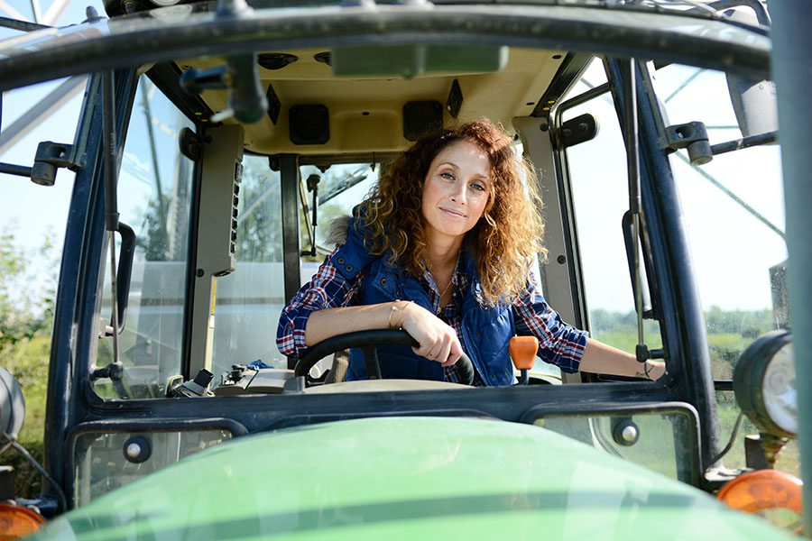 Business Insurance - Portrait of a Middle Aged Woman Sitting in a Tractor on a Sunny Day on the Farm