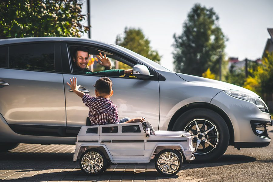 Contact - View of Father Driving in His Car Waving to his Son as His Son Waves Back While Sitting in a Toy Car