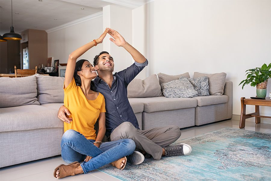 Insurance Quote - Portrait of a Cheerful Young Married Couple Sitting on a Rug in the Living Room While Dreaming of Their Future House