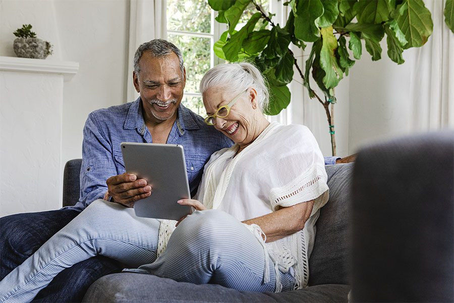 Medicare - Portrait of a Cheerful Elderly Couple Sitting on the Sofa at Home While Using a Tablet Together