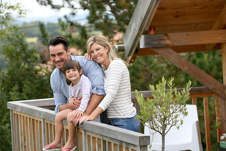 Personal Insurance - Portrait of Cheerful Parents and Their Daughter Standing on the Balcony of a Wooden Home Enjoying the View of the Forest