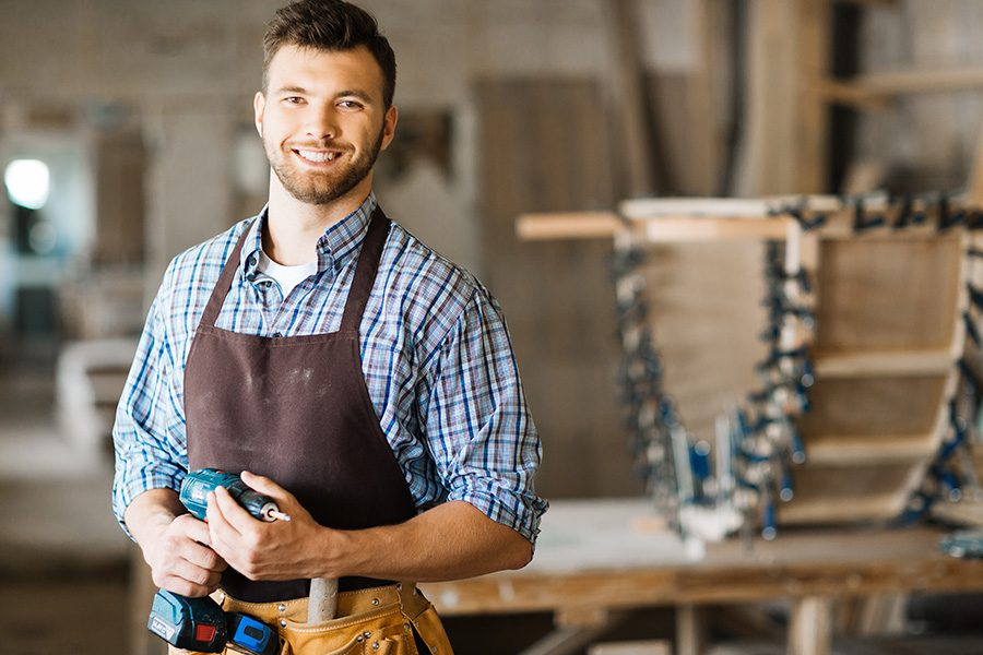 Specialized Business Insurance - Portrait of Smiling Bearded Craftsman With Electric Drill in Hands Standing in Spacious Workshop