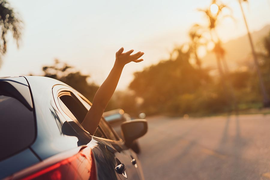 About Our Agency - Hand Waving on the Window of a Car Driving Along a Winding Road at Sunset
