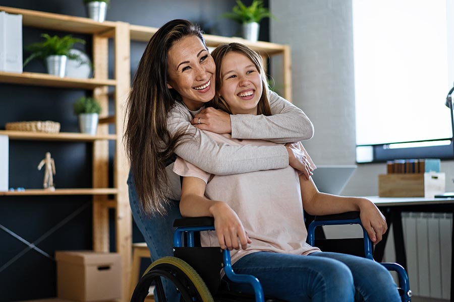 Client Center - Mom Hugs Young Daughter in a Wheelchair, Both Smiling