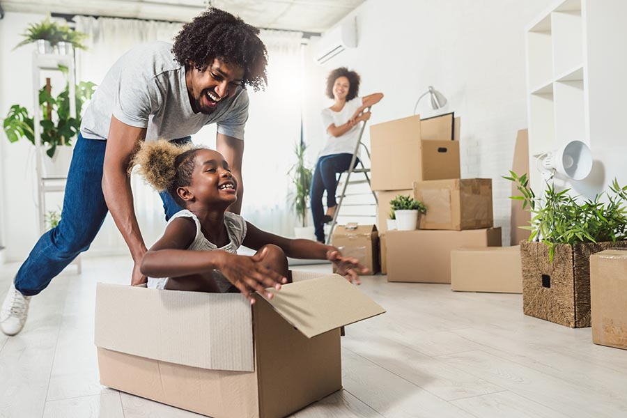 Personal Insurance - Dad Pushes Happy Daughter in a Cardboard Moving Box Along Their Floor, Moving Boxes All Around