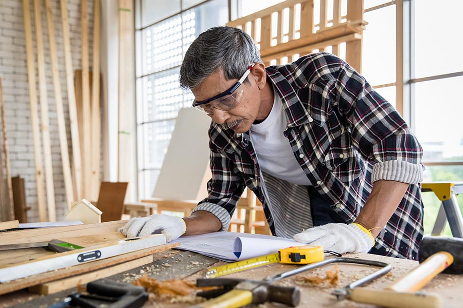 Specialized Business Insurance - Contractor Measures Lumber in a Workshop, Wearing Safety Equipment