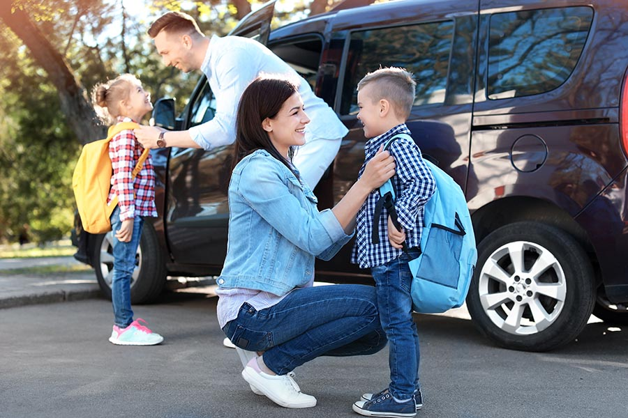 Blog - Parents Getting Their Kids Ready For School in Front of Their Large SUV