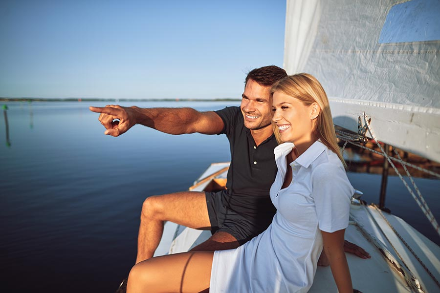 Personal Insurance - Young Couple On a Sailboat on Flat Water on a Sunny Day