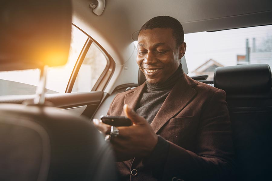 Client Center - Stylish Man Being Chauffeured While Using His Phone and Smiling