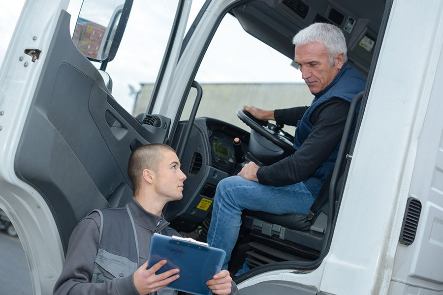 Business Insurance - Senior Truck Driver Sitting in White Truck and Talking to Logistics Manager About the Upcoming Trip