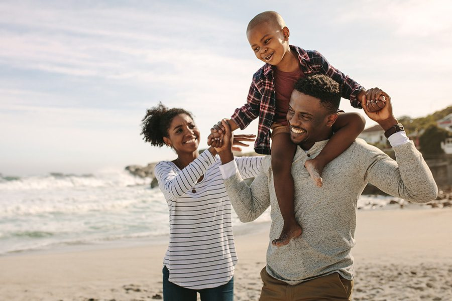 Employee Benefits - Happy Parents Carrying Son on Their Shoulders on a Beach During Their Vacation on a Sunny Day