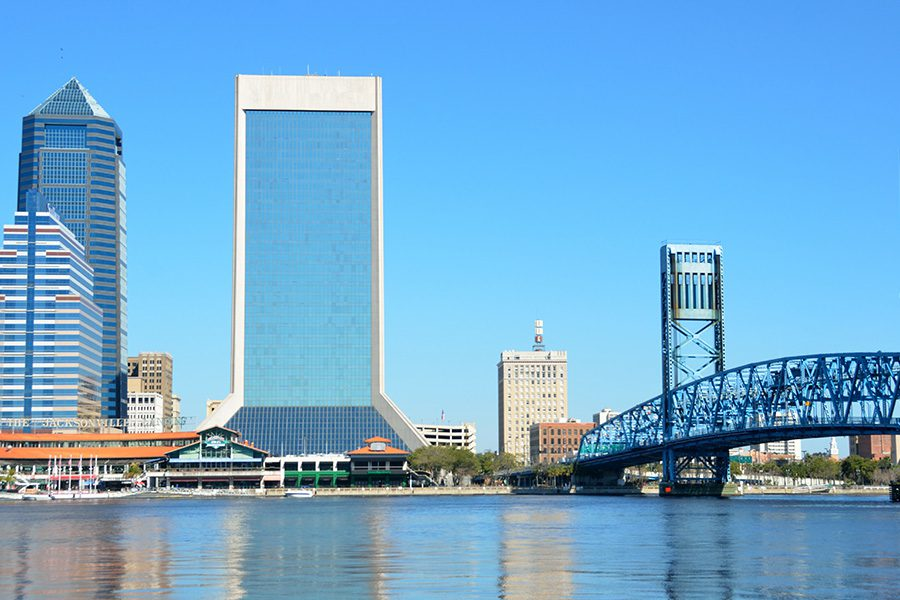 Jacksonville, FL - Far View of Jacksonville Florida Cityscape Displaying Tall Buildings, a Bridge, and the Ocean